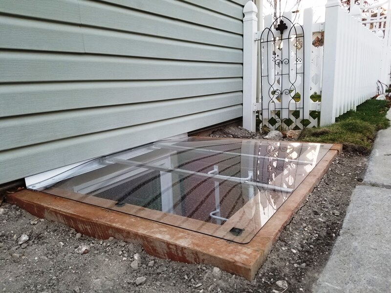 sloped window well cover with uv-resistant polycarbonate on a timber well