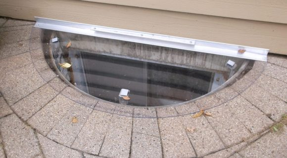sloped polycarbonate cover on a paver well