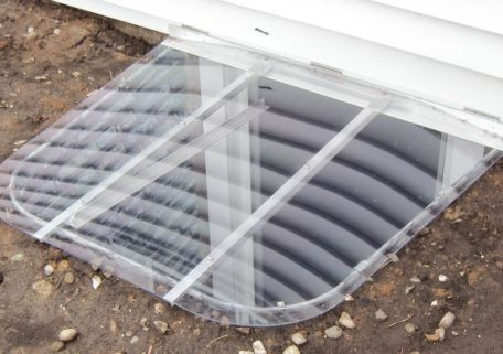 Sloped egress window well cover with hinges and a prop-up bar.