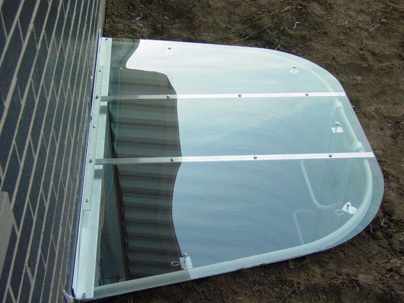 sloped polycarbonate cover on a metal well with crystal-clear surface