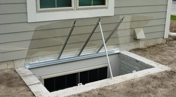 sloped cover on concrete well with open optional pop-bar and hinge