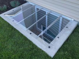 """Large egress cover with 3"""" overlap, installed on a concrete window well. The cover is custom-fitted to the well."""