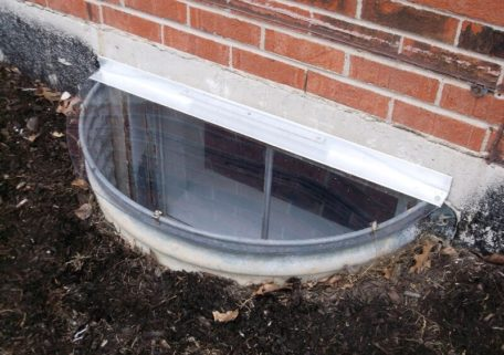 semicircle window well cover on a metal well with uv-resistant polycarbonate