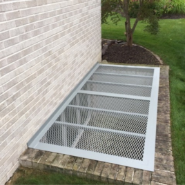 large aluminium grate on a concrete window well