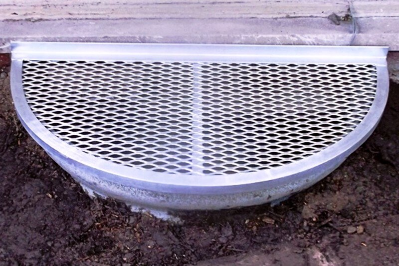 Small metal window well cover on a semi-circle well
