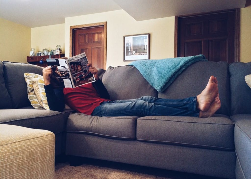 Guy reading a newspaper while laying on couch